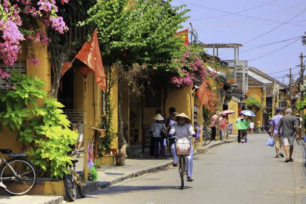 une femme va à vélo dans l'ancienne de Hoi An au centre du vietnam